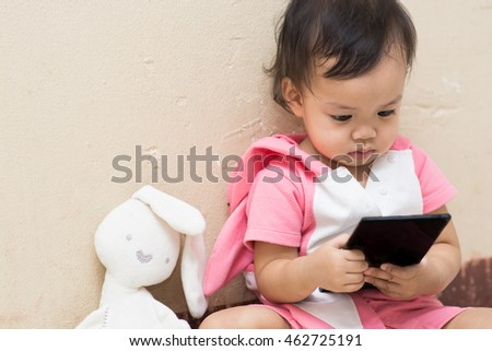 Cute baby and rabbit doll play smart phone with space,focus on her eye