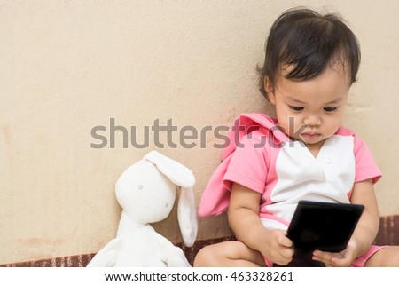 Cute baby and rabbit doll play smartphone with space,focus on her eye