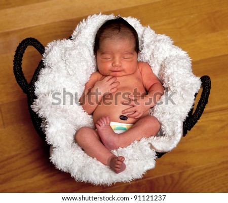 Cute baby asleep in basket with soft lining holding his belly. - stock photo