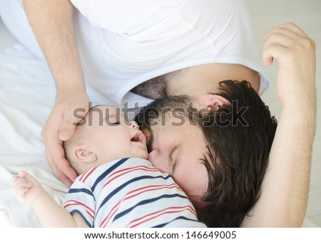 Cute baby at home with father playing