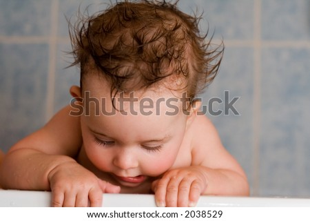 Cute baby bathing. Looks like a cupid looking down. - stock photo