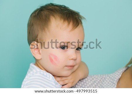 Cute baby blond boy kid child with serious look and red kiss trace on cheek sits on blue wall