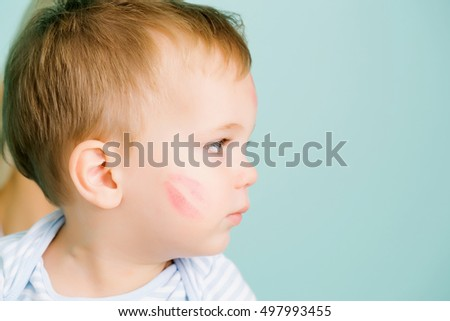Cute baby blond boy kid child with serious look and red kiss trace on cheek sits on blue wall, copy space