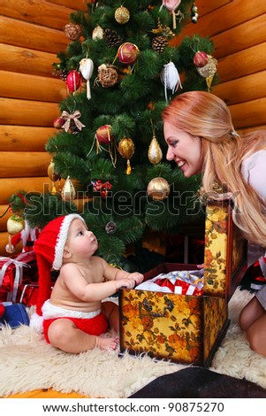 Cute baby boy and his mother against Christmas tree. The baby sitting in front of open case with gifts. - stock photo