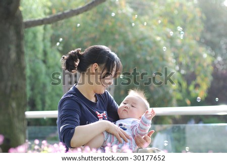 Cute baby boy and  his mother in park with bubbles inbackground