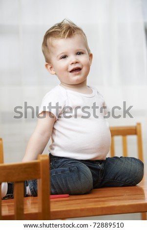 Cute baby boy at 18 months wearing jeans and t-shirt sitting on table at home. - stock photo
