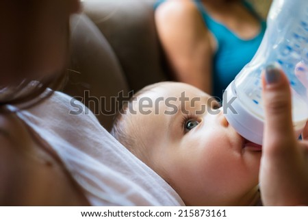 Cute baby boy being fed milk by his mother in a home setting. - stock photo