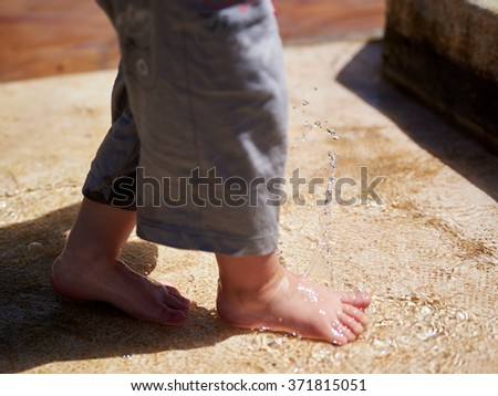 Cute baby boy child plays with water and splashes sprinkles with foot - stock photo