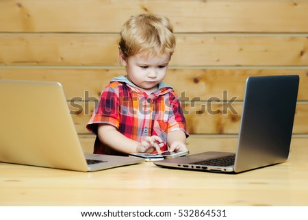 Cute baby boy child with blond curly hair plays on two phones and laptop computers on wooden background