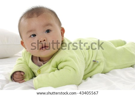 Cute baby boy crawling for on top of a bed