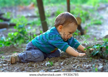 cute baby boy digging the ground in spring forest - stock photo