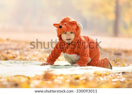 Cute baby boy dressed in fox costume in autumn park - stock photo