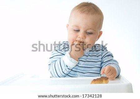 cute baby boy eating biscuits, on white - stock photo