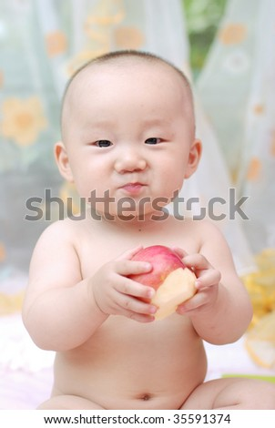 cute baby boy  eating  red apple with tears in eyes - stock photo