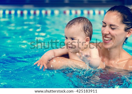 Cute baby boy enjoying with his mother in the pool. - stock photo