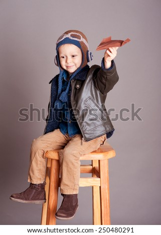 Cute baby boy holding with origami plane in room over gray. Wearing stylish leather jacket. Smiling kid. Childhood. Sitting on wooden chair. - stock photo