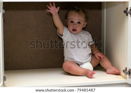 Cute baby boy in a cupboard - stock photo