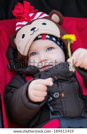 cute baby boy in a stroller holding dandelion in the hand spring time - stock photo