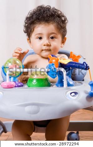 cute baby boy in animal shape baby walker - stock photo