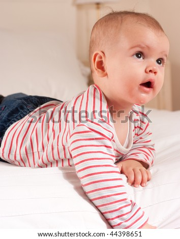 Cute baby boy in jeans and striped t-shirt lying on a bed looking up - stock photo
