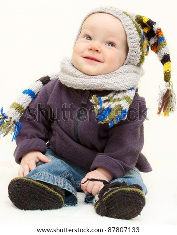 Cute baby boy in knitted handmade hat, scarf and bootees is sitting  with happy smiling face - stock photo