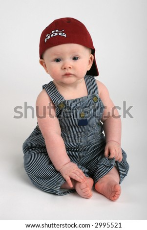 cute baby boy in overalls and hat - stock photo