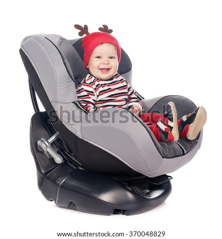cute baby boy in safety car seat over white background