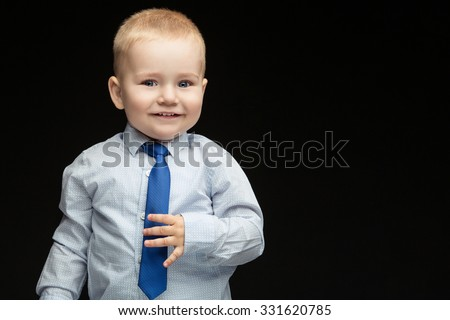 Cute baby boy in shirt, vest holding his blue tie.  Isolated over black background. Copy cpace. - stock photo