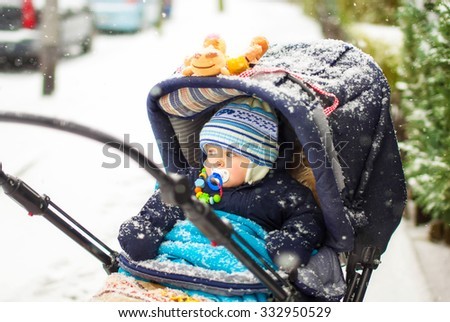 Cute baby boy in warm clothes in pram during winter snow fall on cold winter day. Happy carefree childhood. - stock photo