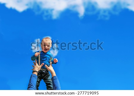 Cute baby boy is being thrown up like little angel is falling from he sky and arms are catching him.  - stock photo