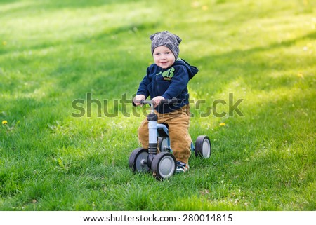Cute baby boy learning to ride his first running bike in a park