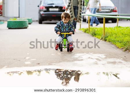 Cute baby boy learning to ride his first running bike in a park - stock photo