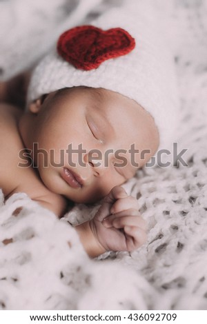 Cute baby boy lie naked on a beige background wearing a crochet viking hat - stock photo