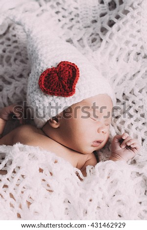 Cute baby boy lie on a beige background wearing a crochet hat - stock photo