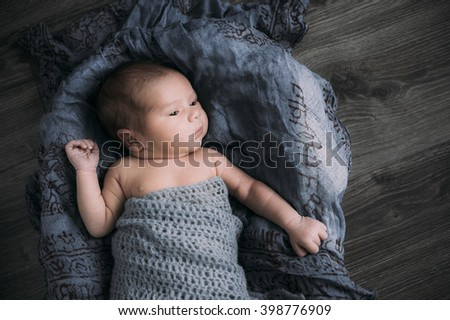 Cute baby boy lie on a beige background wearing a crochet hat in a basket - stock photo