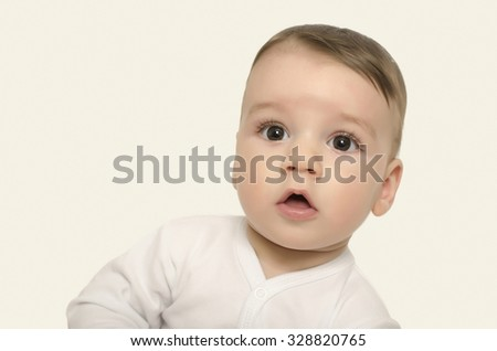 Cute baby boy looking surprised. Adorable baby portrait looking curious isolated on white. - stock photo