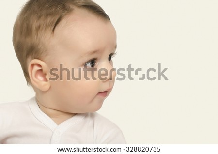 Cute baby boy looking to the side. Adorable baby portrait looking curious isolated on white. - stock photo