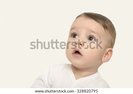 Cute baby boy looking up surprised. Adorable baby portrait looking curious isolated on white. - stock photo