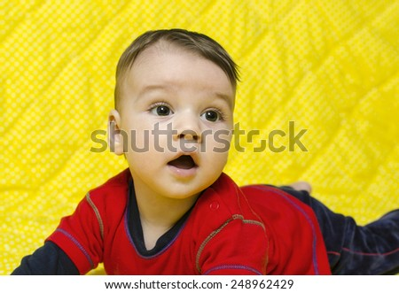 Cute baby boy looking up surprised. Baby lying on his tummy looking curious. - stock photo