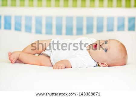 Cute baby boy lying on back. - stock photo
