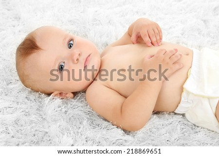 Cute baby boy lying on carpet in room - stock photo
