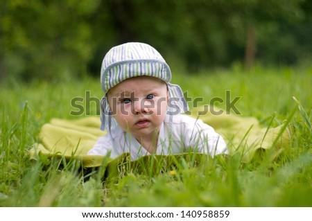 Cute baby boy lying on grass - stock photo
