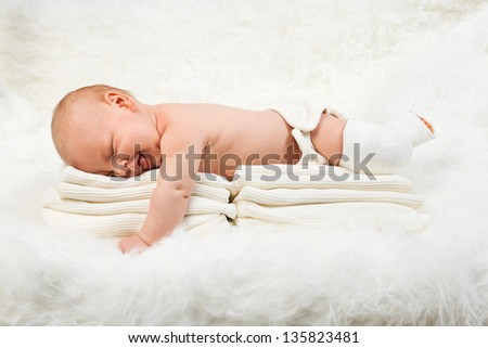Cute baby boy lying on stack of towels - stock photo