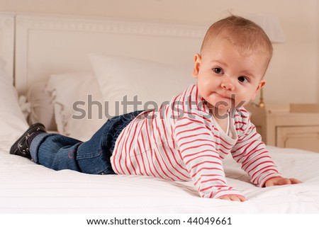 Cute baby boy on a bed trying to crawl - stock photo