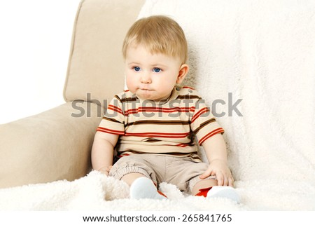 Cute baby boy on sofa, on light background