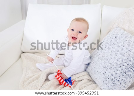 Cute baby boy on white couch with American flag, closeup