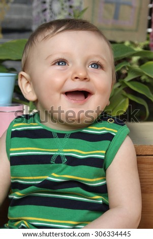 Cute baby boy outside in the garden wearing green outfit - stock photo