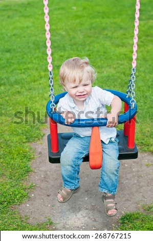 Cute baby boy playing on swing in park - stock photo