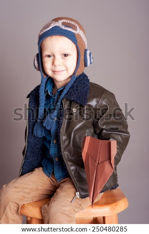 Cute baby boy playing with origami plane in room over gray. Wearing stylish leather jacket. Smiling kid. Childhood.  - stock photo