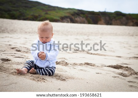 Cute baby boy playing with sand on the beach